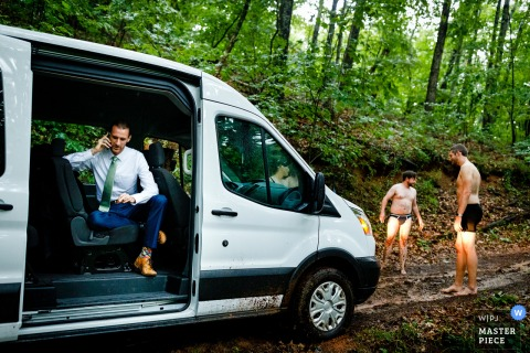 North Carolina wedding photography from Asheville, NC of The groom calling for a tow truck as his groomsmen try to make a way for the van