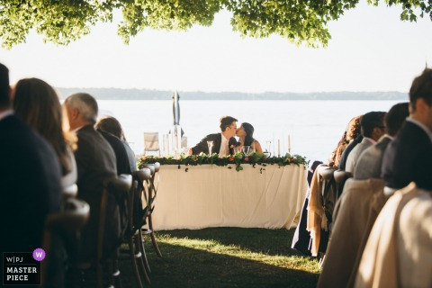 Chicago wedding photography from the outdoor Reception	of the Couple kissing by the water under the trees