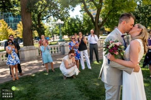 Imagen de la boda del Capitolio del Estado de Wisconsin del primer beso de los novios en el césped