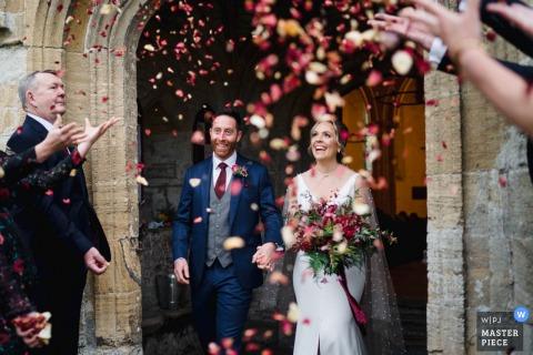 Foto di matrimonio nel Regno Unito di una coppia che esce da una chiesa nel Wiltshire, in Inghilterra
