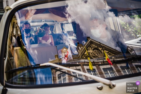 A wedding photographer in Limburg created this image of the couple waiting inside a vintage van outside the building