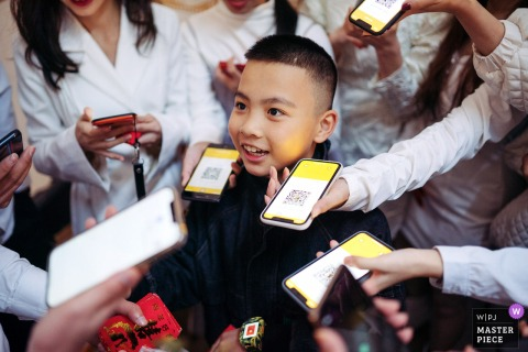 A top wedding photographer in Guangxi captured this picture of a young boys face surrounded by phones with QR codes
