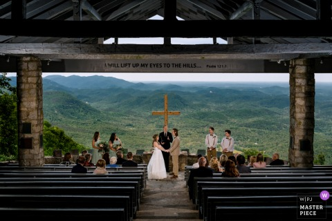 Best wedding photography from Greenville, SC showing a pic ofthe ceremony, but using OCF flash to capture the backdrop in the image due to very little light at Pretty Place Camp