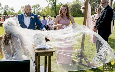 A top wedding photographer in Raymore, Missouri captured this picture ofa very long veil, a centerpiece of her wedding day attire, was lovely in every way except that a wind picked up and the communion cup spill-eth over