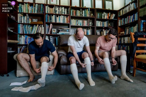 A wedding photographer in Nar Nar Goon, Victoria created this image ofgroomsmen in Australia Getting ready putting on tall, long socks