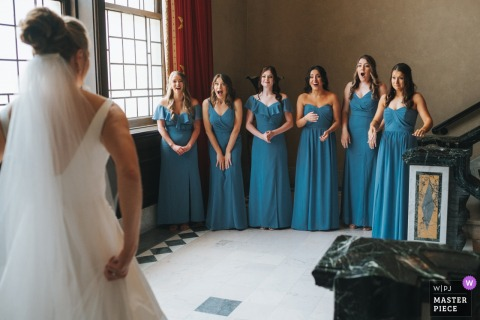 A Cleveland wedding photographer in Ohio created this image ofthe First look reaction of the bridesmaid of bride in her gown