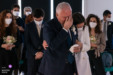 A top Mantua wedding photographer in Quistello captured this picture at Centro Hub Oltrepo Mantovano of the The brides father, in the moment of remembering his mother who has recently disappeared, bursts into tears and bride breaks away from the groom