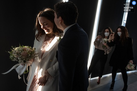 A wedding photographer in Quistello, Mantua created this image at the Centro Hub Oltrepo Mantovano of the bride and groom go to the exit, meanwhile the groom whispers something in the ear of the bride, Meanwhile, the witnesses are looking for a pic