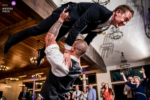 A Boulder wedding photographer at Black Canyon Inn in Estes Park created this image ofa Colorado best man lifting groom into the air
