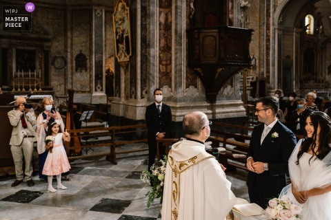 A wedding photographer in Puglia created this image ofthe flower girl inside the church gesturing to the bride and groom