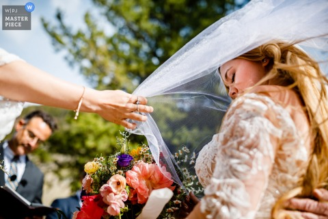 A top wedding photographer in Summit County, CO captured this picture ofa blowing veil while in Prayer during the outdoor ceremony