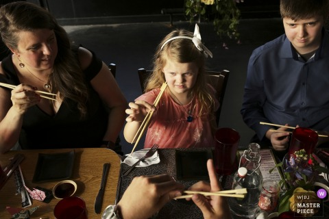 A wedding photographer at the Verb Hotel in Boston created this image of kids learning chopsticks at reception