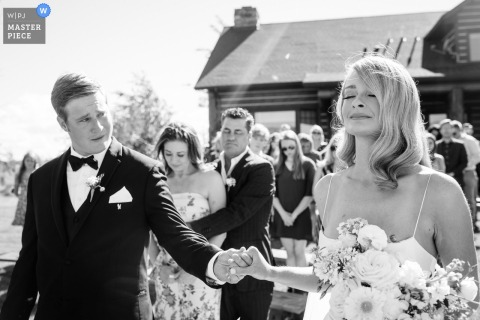 Un des meilleurs photographes de mariage à Belgrade, Montana a capturé cette photo d'un marié jetant un coup d'œil pendant la prière