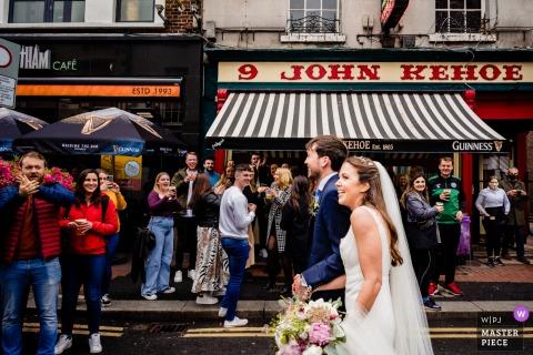 Dublin City beste trouwreportagefotografie in Ierland met een foto van een menigte feestvierders die buiten drinken tijdens Covid-regels reageren op het zien van de pasgetrouwden