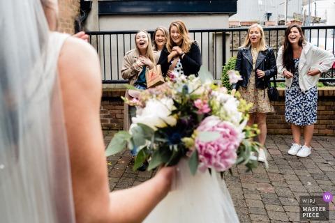 Een topfotograaf voor trouwreportages in Dublin, Ierland maakte deze foto van Vrienden die buiten stonden te wachten tijdens de ceremonie om de bruid te feliciteren