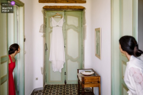 A wedding photographer at the Domaine Fon de Rey in Herault created this image of the bride and bridesmaid inspecting the hanging bridal gown over a door