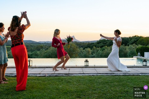 A French wedding photographer at Mas Saint Germain created this image showing The witness caught the bouquet from the brides toss