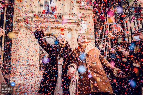 A wedding photographer at the Paris City Hall created this image showing Bride and groom are going out of the city hall, guests are throwing confetti