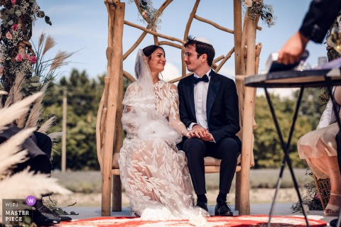 A top Solerieux wedding photographer at Les Domaines de Patras captured this picture ofthe Complicity look between the Bride and Groom during the outdoor ceremony