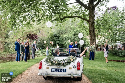 A wedding photographer in Alphen aan den Rijn created this image ofthe bride and groom waving goodbye after the wedding as they drive away in convertible car