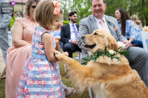Georgia best wedding photography from the Lake Lanier Islands showing a pic showing The ring bearer paws the flower girl at outdoor ceremony