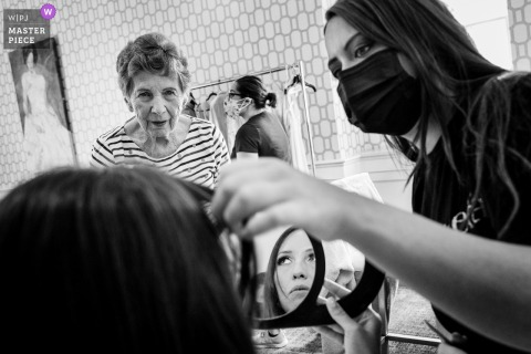 A wedding photographer at a Pennsylvania hotel created this image ofBride getting her touch ups done under the close eye of her grandma