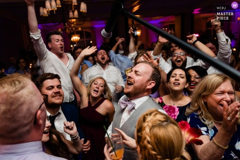 A top wedding photographer in Pennsylvania captured this picture of The groom leading the chorus in singing along with the band