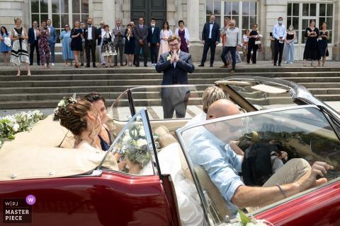 Un grand photographe de mariage à Limoges a capturé cette photo de l'arrivée de la mariée à l'arrière d'une voiture vintage décapotable