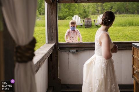 La migliore fotografia di matrimonio del Massachusetts da Valley View Farm a Haydenville che mostra una foto di un giovane ospite al ricevimento con la sposa in primo piano