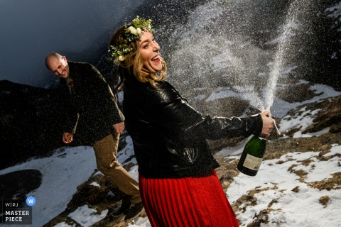 A Colorado wedding photographer in the Rocky Mountain National Park created this image of  A couple sharing some champagne after drenching the groom with it