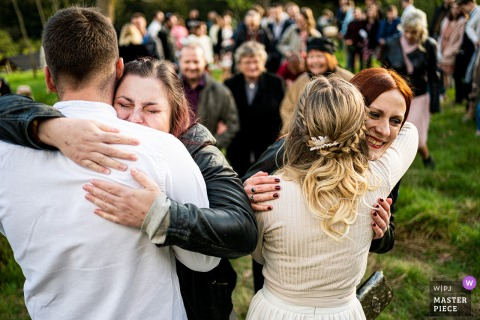 A top Czech wedding photographer in Beskydy captured this picture ofCongratulatory hugs outdoors after the ceremony