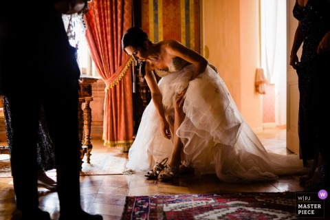 Best Italy wedding photography from Castello di Torre Alfina showing a pic ofThe bride  putting on her shoes