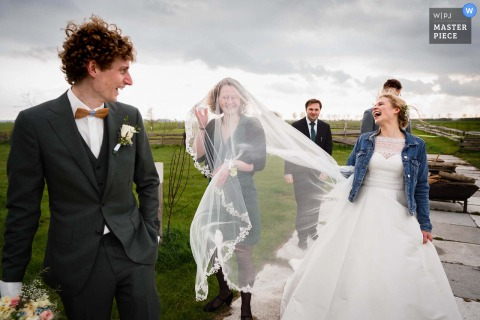 A top wedding photographer in the Netherlands captured this picture showing It was windy that day and the brides friend had a funny moment with the veil which took of by the wind