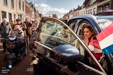 A top Netherlands wedding photographer in Vianen, just outside city hall, captured this picture ofThe bride giving a handkiss to someone in the audience while everybody is celebrating their marriage
