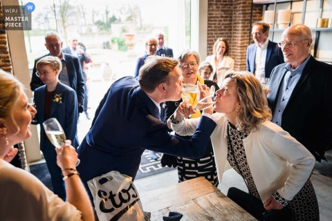 Best Netherlands wedding photography from Buitenplaats Amerongen showing a pic ofThe groom drinking champagne with a family member