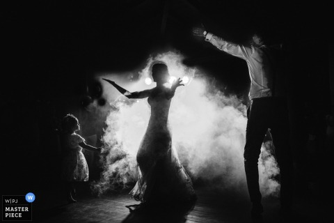 A Portugal wedding photographer in Ponte de Lima created this image of the bride and groom dancing in fog and lights