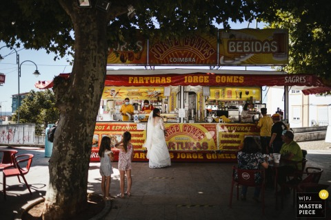 A top Portugal wedding photographer in Coimbra captured this picture ofthe bride at a street vendor food station