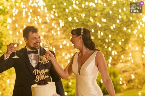 Best wedding photography from Castello di Rossino showing a pic ofthe bride and groom toasting by the cake in front of fireworks