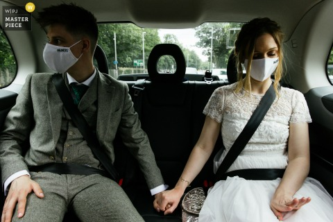 Best wedding photography from France showing a pic ofThe couple wearing facemasks whilst the bride looks at her new wedding ring
