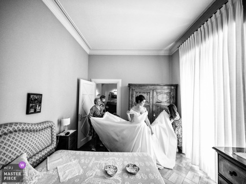 Milano wedding photography of 4 women and a wedding dress, none of them manage to remove the pleats from the skirt