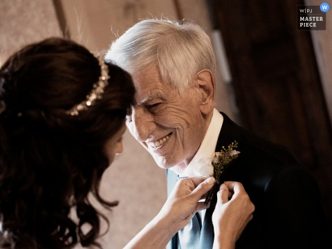 A top Castello di Cernusco wedding photo in Lombardone capturing this picture of the bride pinning the flower in her buttonhole to her father, he gazes at her entranced