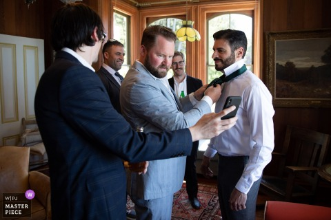 A wedding photographer at Switzer Farm in Mendocino, CA created this image of groomsmen tying the grooms tie using the internet as a guide