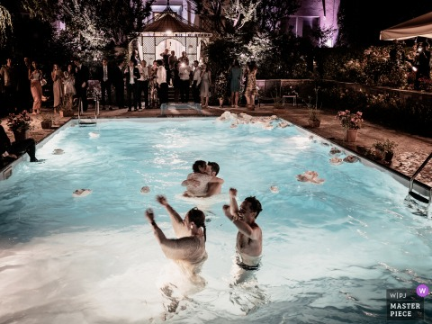 A top wedding photographer in Casalpusterlengo captured this picture showing the wedding party is almost over and the bride and groom kiss in the pool, exhausted but happy