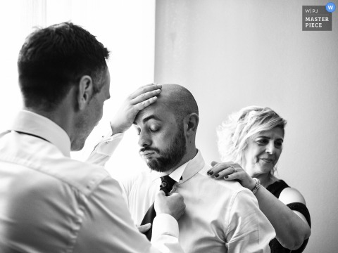 Best wedding photography from Milan showing The mother and the best man helping him fix the tie but at that moment the tension is felt and the groom cant take it anymore