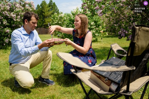 A top wedding photographer at the Montreal Botanical Garden captured this picture of a Wedding couple cutting a pie in front of a laptop in the middle of a garden