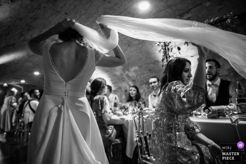 Best wedding photography from Grand Est showing a pic ofthe brides veil wrapping up guests at the reception