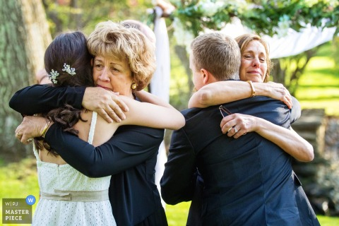 A wedding photographer at Appleford Estate in PA created this image ofa mothers hug their children after intimate ceremony outdoors