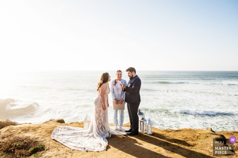 A top wedding photographer at Sunset Cliffs in San Diego captured this picture showing the bride laughs during vows during intimate beach ceremony