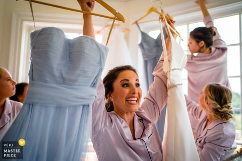 A wedding photographer at the Mt. Ida Farm created this image showingA bridesmaid excitedly carries bridesmaid dresses