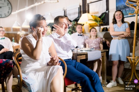 Best wedding photography from Bordeaux, France showing a pic ofThe Bride and Groom wiping down tears at the same time during a video projection